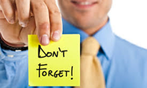 Man with a blue shirt holding a yellow note with the words Don't forget